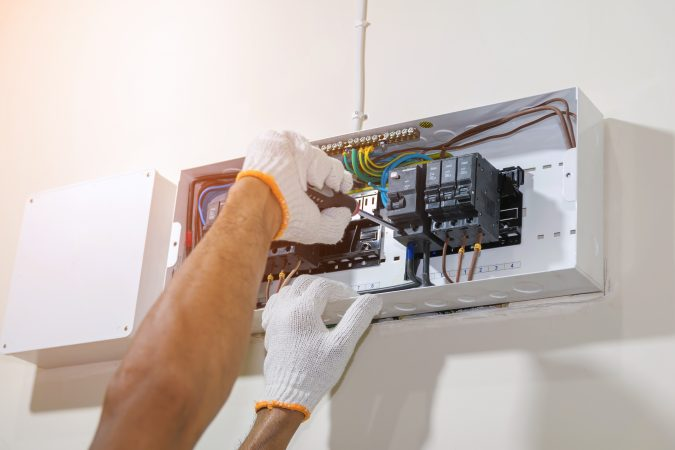 Closeup of hands of electrician using a screwdriver to tighten the circuit breaker to prevent power supply to the control box.